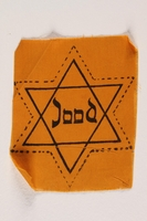 2006.476.2 front Unused yellow Star of David badge printed with Jood  Click to enlarge