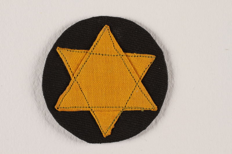 2007.235.1 front Badge with a yellow Star of David on a black circle worn by a Romanian Jewish woman