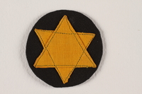 2007.235.1 front Badge with a yellow Star of David on a black circle worn by a Romanian Jewish woman  Click to enlarge