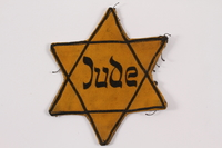 2015.323.2 front Star of David badge printed Jude worn by a Jewish prisoner in Terezin  Click to enlarge