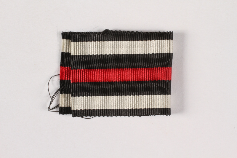 2015.415.9 front Piece of black, white and red striped ribbon awarded to a Jewish German veteran