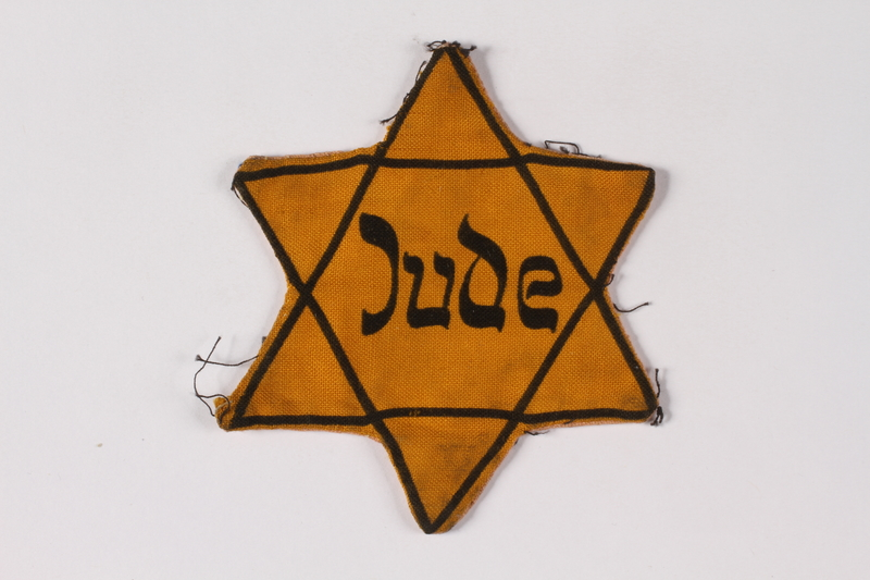 2001.3.4 front Star of David badge on floral backing printed Jude owned by a Czech Jewish survivor