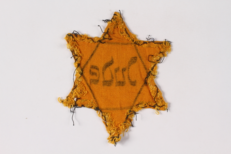 2001.3.4 back Star of David badge on floral backing printed Jude owned by a Czech Jewish survivor
