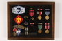 Shadow box containing mounted military medals and insignia of a US Army Captain