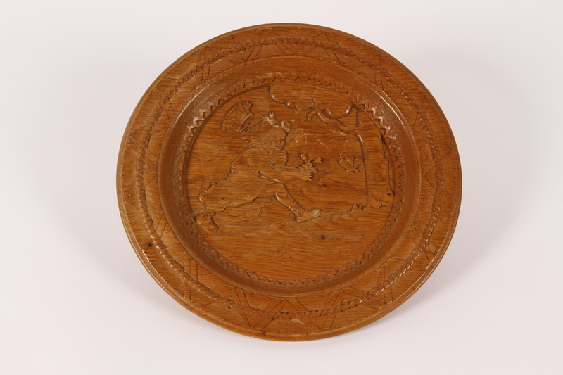 2015.451.52 front Wooden plate picturing a girl chasing butterflies made in a displaced persons camp