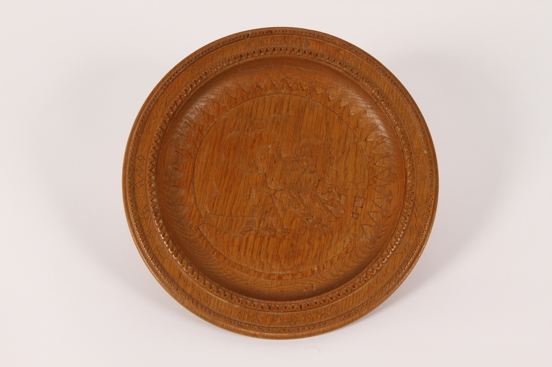2015.451.53 front Wooden plate with a carving of a man and a horse made in a DP camp