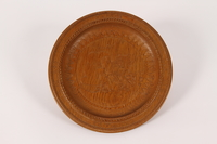 2015.451.53 front Wooden plate with a carving of a man and a horse made in a DP camp  Click to enlarge