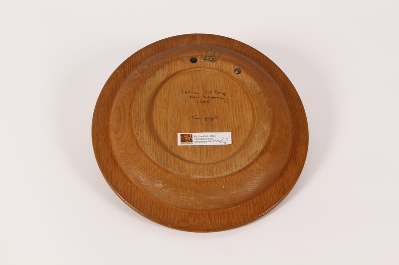 2015.451.53 back Wooden plate with a carving of a man and a horse made in a DP camp