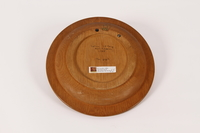 2015.451.53 back Wooden plate with a carving of a man and a horse made in a DP camp  Click to enlarge