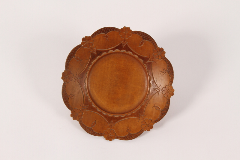 2015.451.57 front Wooden plate with a carved floral rim made in a displaced persons camp
