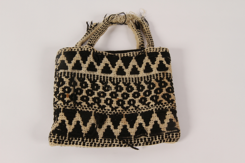 2000.471.2 front Black and white knit bag used in slave labor camps by a Polish Jewish woman