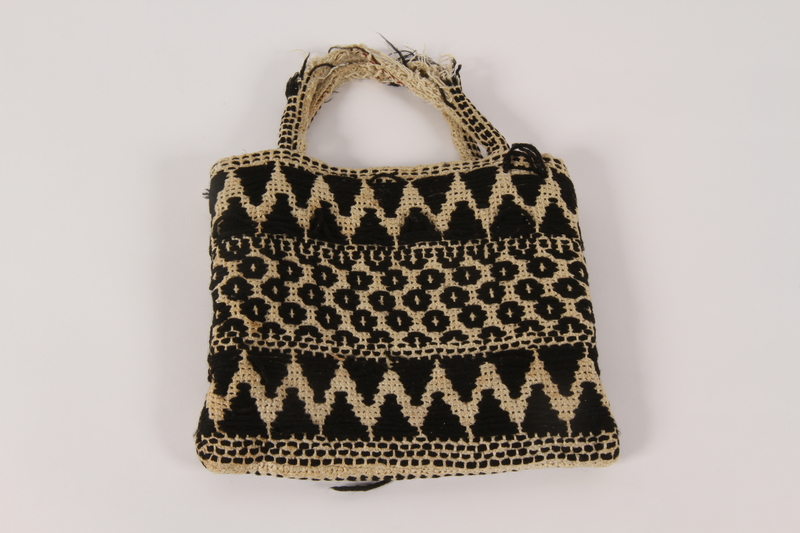 2000.471.2 back Black and white knit bag used in slave labor camps by a Polish Jewish woman