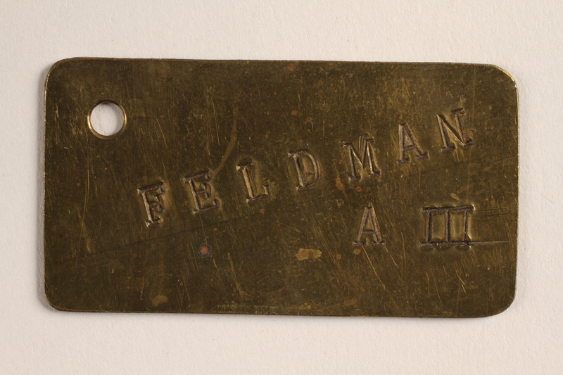 2004.614.10 front Brass tag with name Feldman