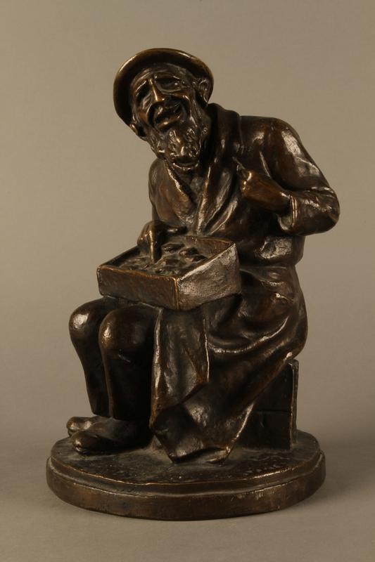 2016.184.2 front Bronze figurine of a seated Jewish peddler