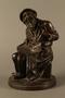 Bronze figurine of a seated Jewish peddler