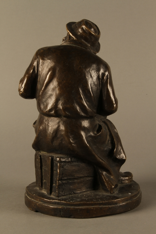 2016.184.2 back Bronze figurine of a seated Jewish peddler