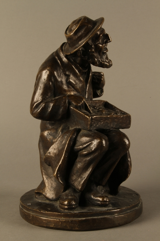 2016.184.2 right side Bronze figurine of a seated Jewish peddler
