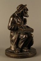 2016.184.2 right side Bronze figurine of a seated Jewish peddler  Click to enlarge
