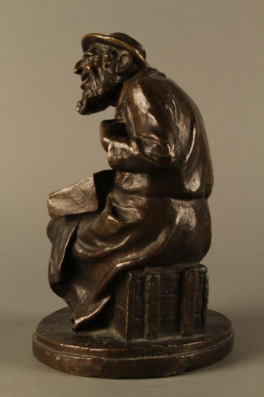 2016.184.2 left side Bronze figurine of a seated Jewish peddler