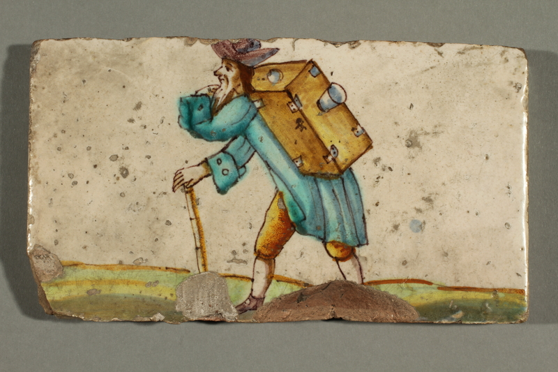 2016.184.9 front Faience tile with an image of a Jewish peddler with a large box on his back