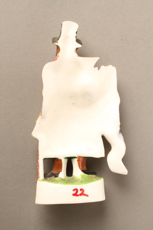 2016.184.20 back Porcelain figurine of a ribbon peddler in a red coat