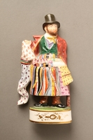 2016.184.20 front Porcelain figurine of a ribbon peddler in a red coat  Click to enlarge