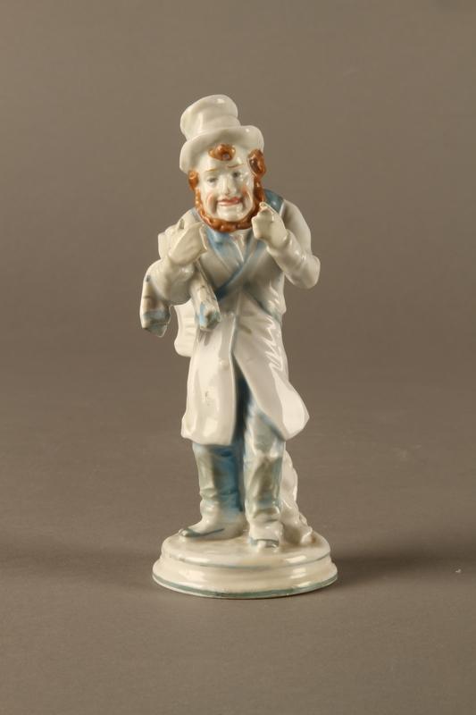 2016.184.10 front White porcelain match holder depicting a stereotypical Jewish peddler