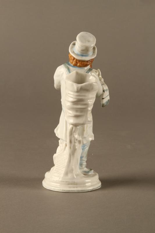 2016.184.10 back White porcelain match holder depicting a stereotypical Jewish peddler
