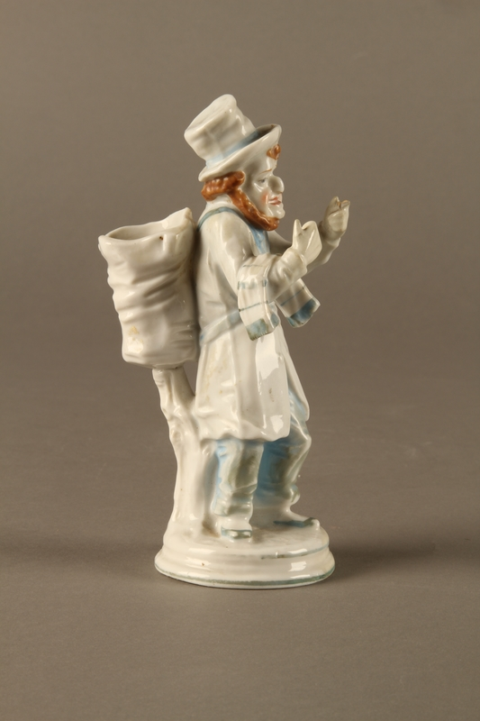 2016.184.10 right side White porcelain match holder depicting a stereotypical Jewish peddler