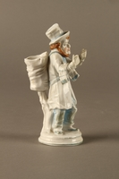 2016.184.10 right side White porcelain match holder depicting a stereotypical Jewish peddler  Click to enlarge