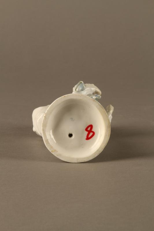 2016.184.10 bottom White porcelain match holder depicting a stereotypical Jewish peddler