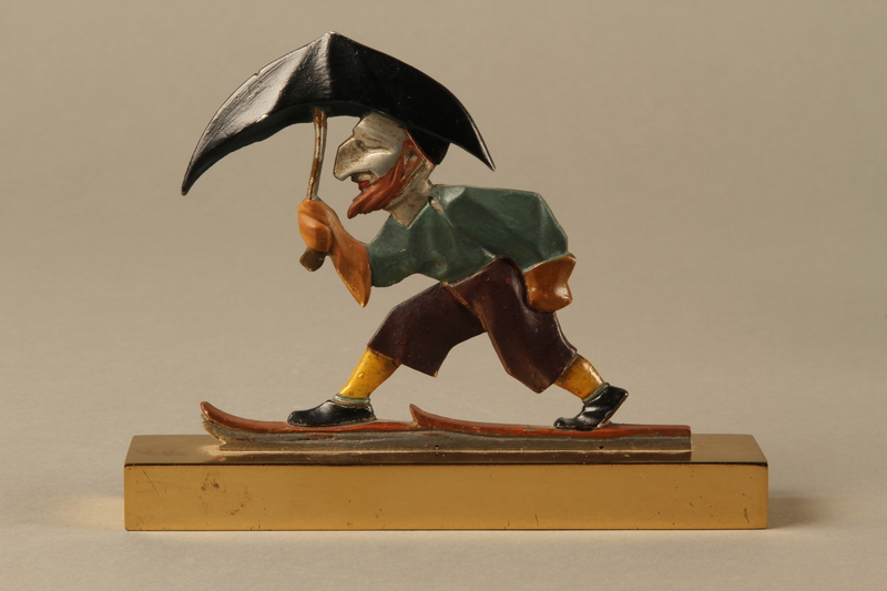2016.184.24 front Painted metal figure of a Jew on skis with an umbrella