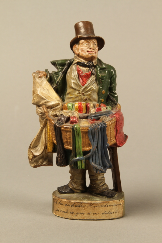2016.184.21 front Terracotta figurine of a Jewish ribbon peddler with a basket of colorful cloth