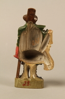2016.184.21 back Terracotta figurine of a Jewish ribbon peddler with a basket of colorful cloth  Click to enlarge