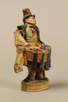 2016.184.21 right side Terracotta figurine of a Jewish ribbon peddler with a basket of colorful cloth  Click to enlarge