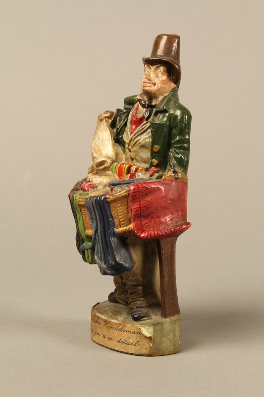 2016.184.21 left side Terracotta figurine of a Jewish ribbon peddler with a basket of colorful cloth