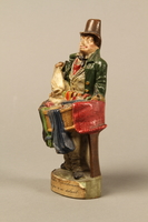 2016.184.21 left side Terracotta figurine of a Jewish ribbon peddler with a basket of colorful cloth  Click to enlarge