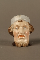 2016.184.29 front Porcelain cup shaped as the head of a sneering Jewish man  Click to enlarge