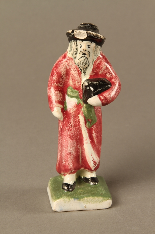 2016.184.30 front Small ceramic figure of a Jewish man in a long red coat