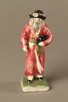 2016.184.30 front Small ceramic figure of a Jewish man in a long red coat  Click to enlarge