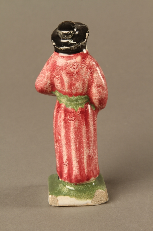 2016.184.30 back Small ceramic figure of a Jewish man in a long red coat