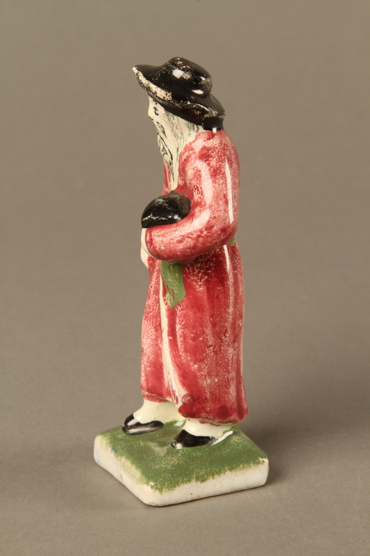 2016.184.30 left side Small ceramic figure of a Jewish man in a long red coat