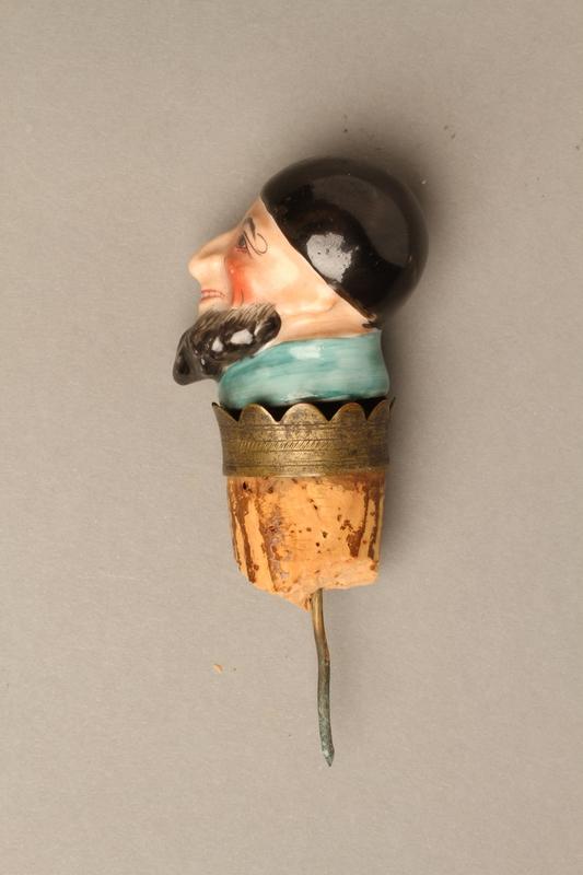2016.184.35 left side Cork bottle stopper with a porcelain head depicting a Jewish steretoype