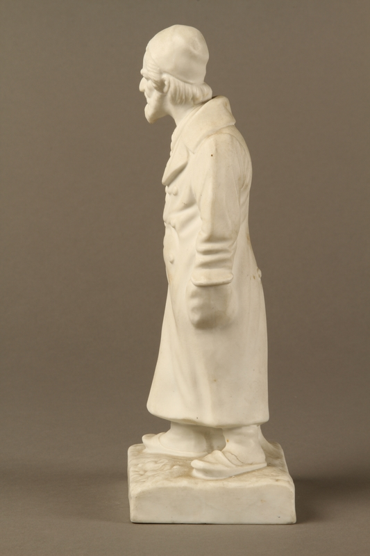 2016.184.39 left side White porcelain figurine of a Jewish matchmaker with his umbrella