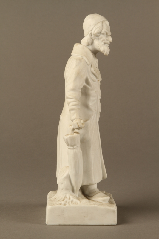 2016.184.39 right side White porcelain figurine of a Jewish matchmaker with his umbrella