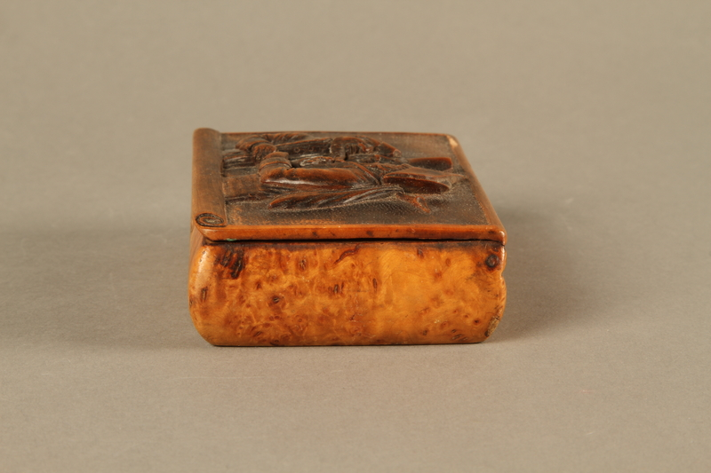 2016.184.42 left side Rosewood snuff box with a carving of three Jewish hareskin dealers