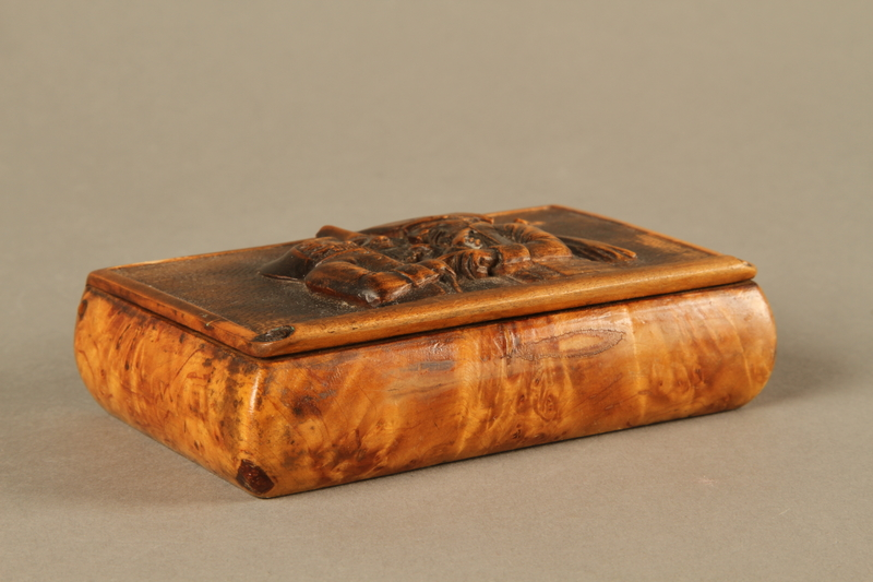 2016.184.42 closed Rosewood snuff box with a carving of three Jewish hareskin dealers