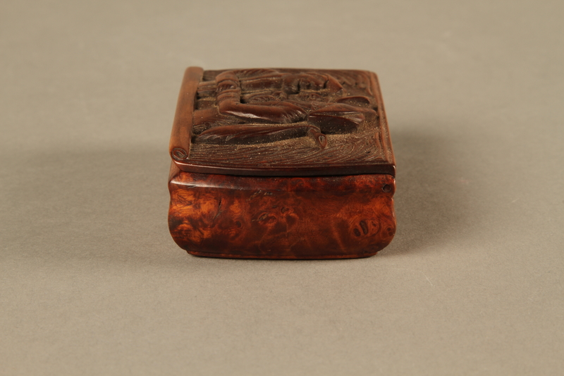 2016.184.43 left side Carved rosewood snuff box with an image of three Jewish hareskin dealers