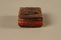 2016.184.43 left side Carved rosewood snuff box with an image of three Jewish hareskin dealers  Click to enlarge