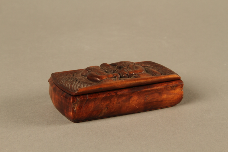 2016.184.43 closed Carved rosewood snuff box with an image of three Jewish hareskin dealers